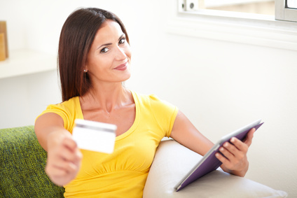 Smiling woman in yellow shirt giving you a credit card while sitting inside the house